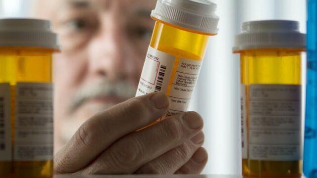 A man reaches for a pill bottle
