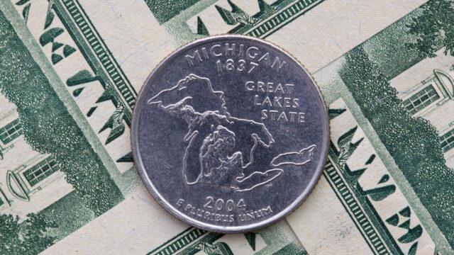 A Michigan quarter sitting on a stack of bills.