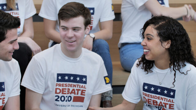 College students shaking hands, wearing 2020 debate t-shirts