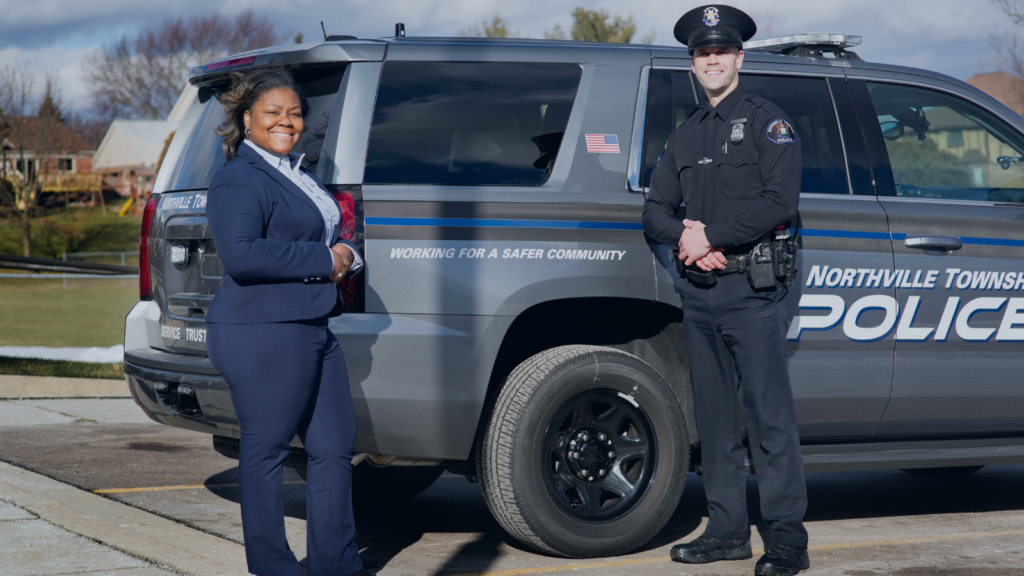 woman in a suit and a male police officer dressed in uniform standing in front of a police SUV