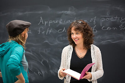Faculty member smiles at student in front of a chalkboard